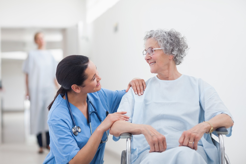 Elderly patient looking at a nurse in hospital ward