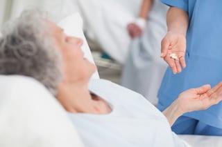 Nurse giving drugs to an elderly patient in hospital ward.jpeg