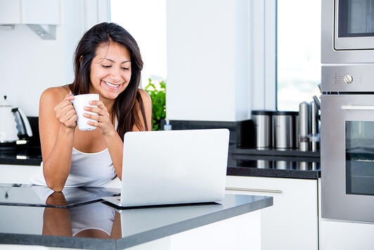 Woman checking her emails in the morning on a laptop